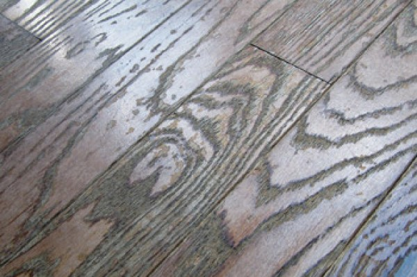 Prefinished solid wood floor damaged by repeated use of a steam mop cleaner